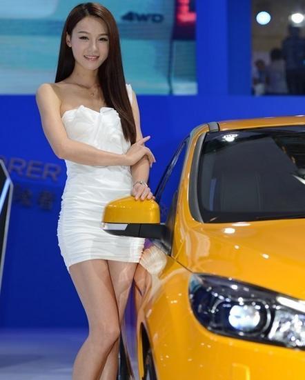 白衣美女车模与黄色汽车相伴